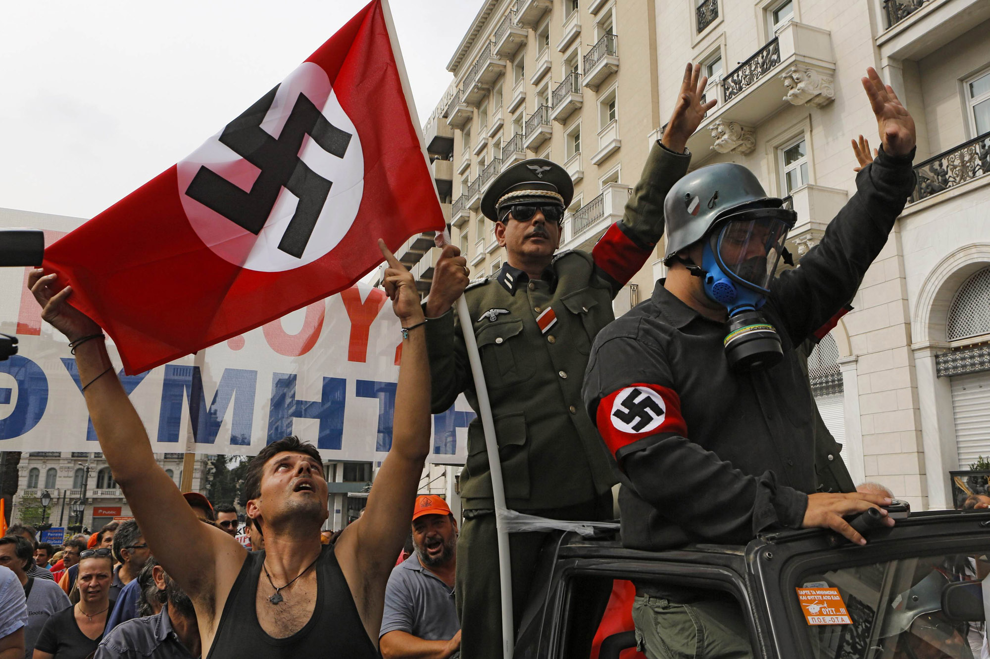 File picture shows demonstrators dressed as Nazis and waving a swastika flag as they ride in an open-top car in Syntagma Square in Athens as they protest against the visit of Germany's Chancellor Angela Merkel